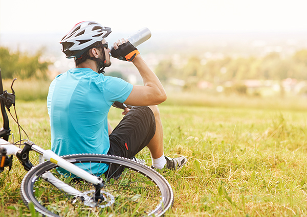 man drinking from a water bottle next to a bicycle