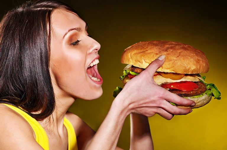 woman holding an oversized hamburger with both hands