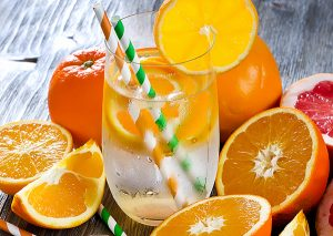 glass of orange infused water surrounded by orange slices