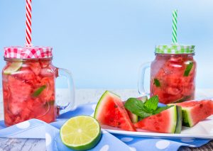 two jars of watermelon infused water next to slices of watermelon