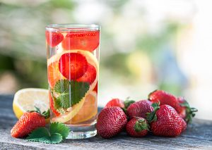 glass of orange and strawberry infused water