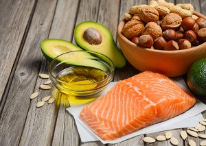 A spread of foods with healthy fats including salmon, olive oil, nuts, and avocado