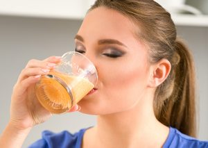 Woman drinking a fruit juice in the morning in her kitchen