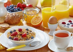 A breakfast spread of muesli topped with fresh fruit, breads, a hard boil egg, yogurt, berries, and orange juice