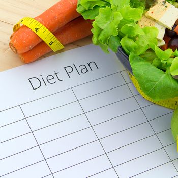 A diet plan piece of paper with a salad, apple, and bunch of carrots