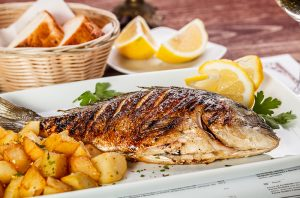 grilled whole fish with potatoes and lemon wedges