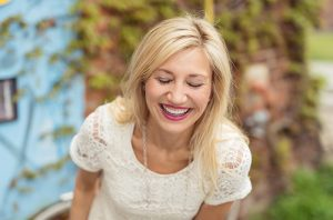 blond woman laughing with eyes closed