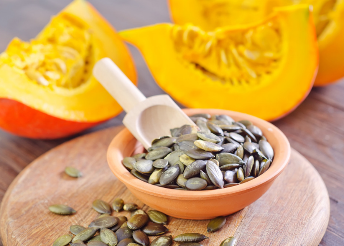 A bowl of pumpkin seeds on a wooden board with fresh cut pumpkin in the background