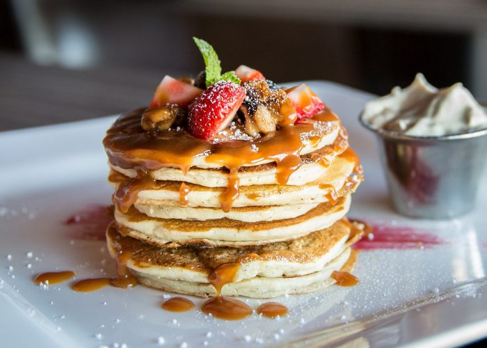 stack of pancakes topped with berries and syrup