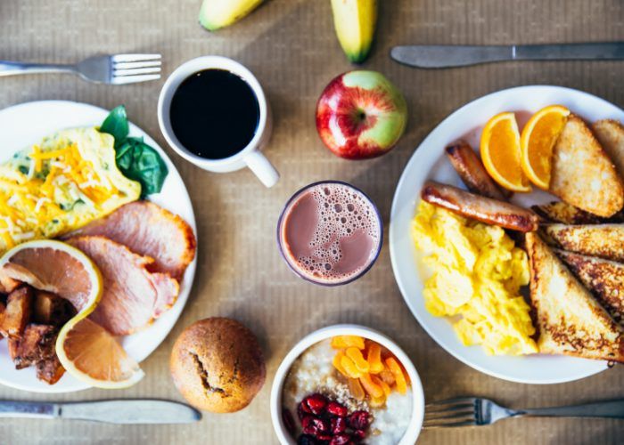 top down view of breakfast plates filled with eggs bacon, fruits, toast, coffee, and juices