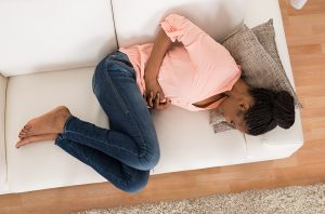 woman on couch clutching stomach with extreme period pain