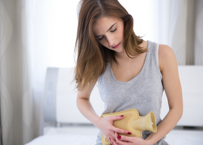 woman holding hot water bottle against abdomen for period pain relief
