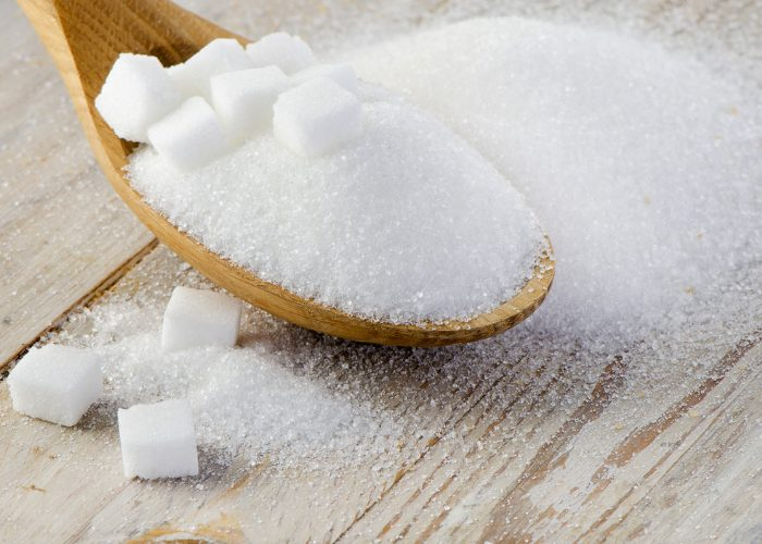 Wooden spoon full of sugar on a wooden table