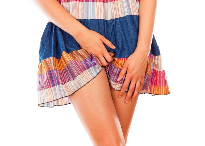 Woman in colorful skirt holding her groin area due to vaginal discomfort caused by yeast infection