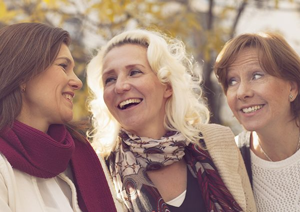 Group of three happy middle-aged women socializing out in a park