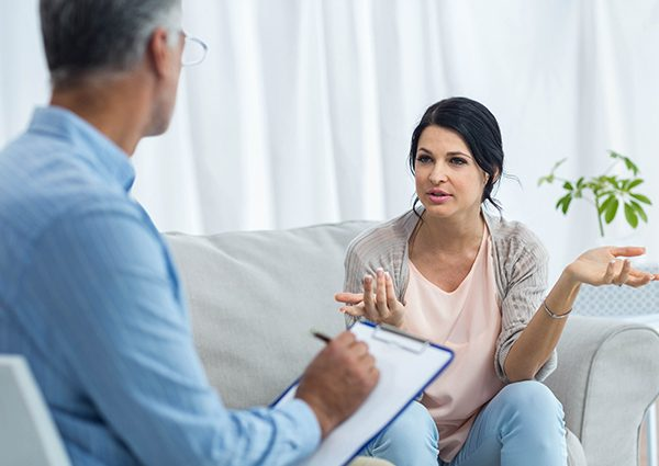 A middle-aged woman talking to her doctor about her opioid addiction and discussing the opioid epidemic.
