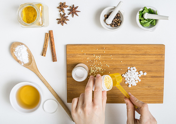 Woman in the middle of making her own DIY beauty products with an assortment of ingredients like honey and star anise on a table