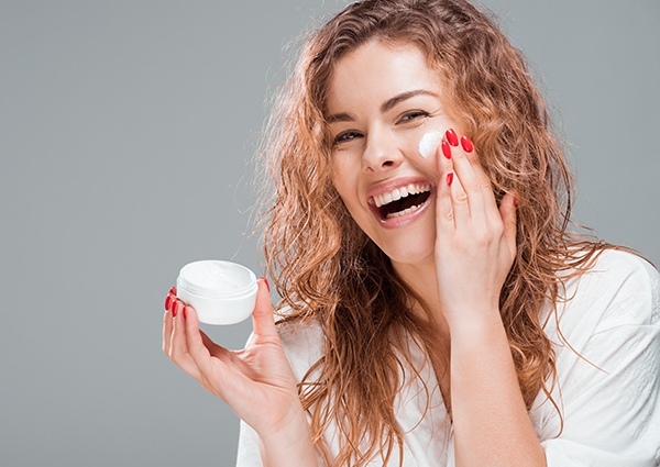 Woman smiling widely as she holds a small jar of her homemade skin cream and applies it to her face