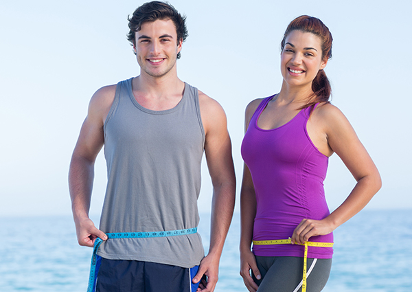 Male and female running partners on the beach holding measuring tapes around their waist