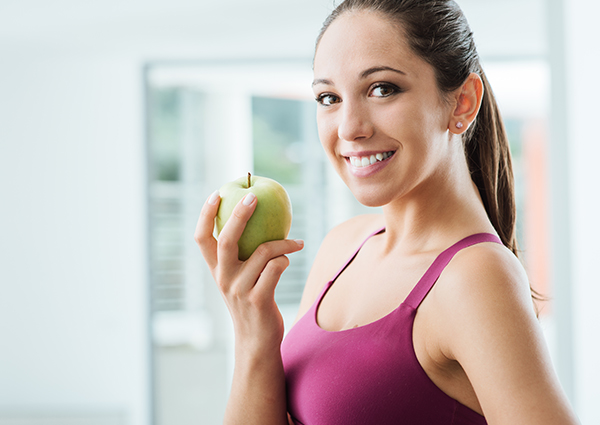 Young woman holding a green apple and smiling in her house