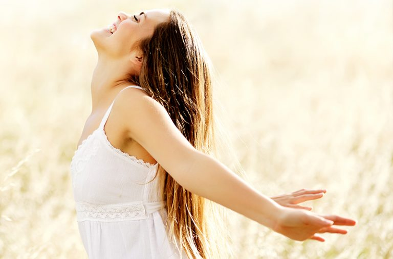Woman in a field stretching back her arms in happiness