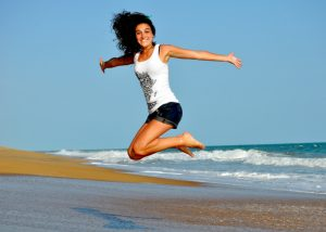 happy woman jumping high on a beach