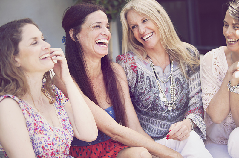 A group of middle-aged women sitting around and laughing