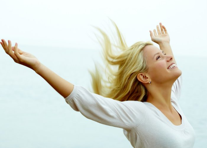Happy smiling woman with her hands up in the air living life to the fullest