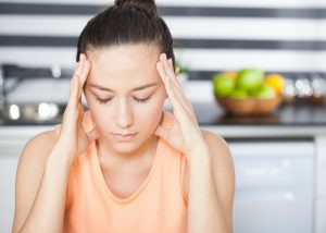 woman having a migraine and holding her head with two hands