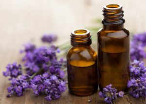 small bottles of lavender oils and purple lavender flowers around