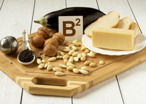 foods rich in vitamin b2 such as eggplant, cheese, almonds, walnuts on cutting board