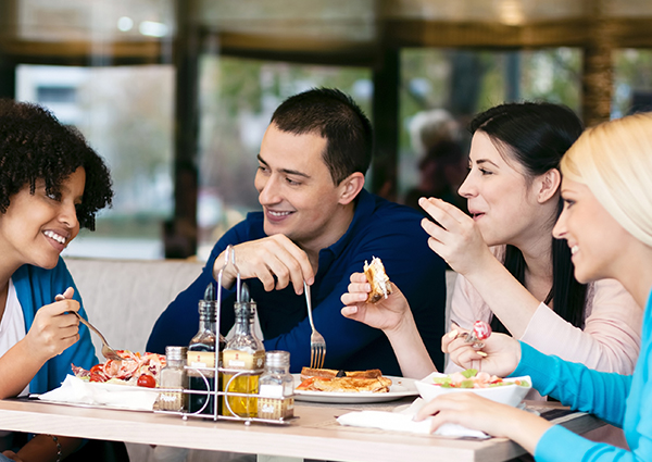 A group of four friends enjoying a meal and conversation at an Italian restaurant