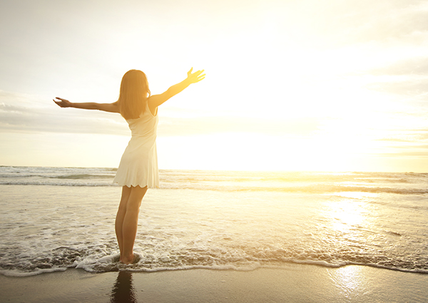 woman standing on a beach with open arms as the sun sets