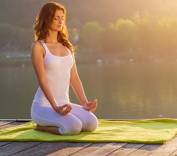 woman kneeling on yoga mat meditating to forget the past