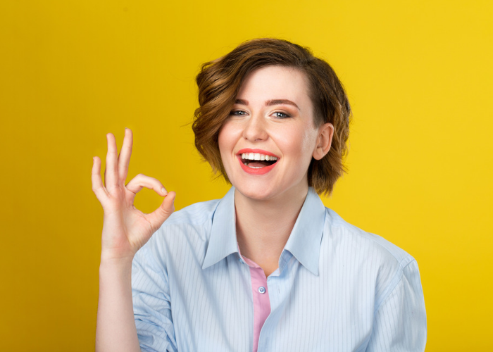 Smiling woman with positive mindset making the ok sign against a yellow background