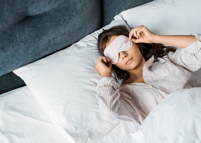 Woman in bed sleeping with eye mask