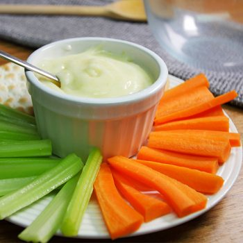 Ramikin of mayonaise on a plate with sticks of celery and carrot, as well as some crackers