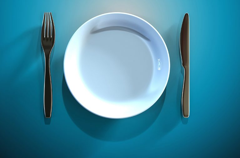 An empty white plate with a fork and knife on the side on a blue table