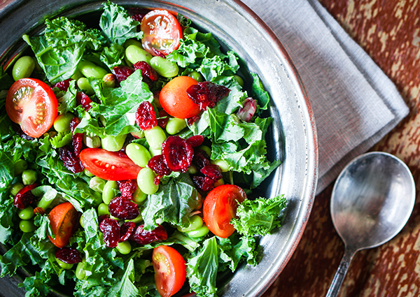 Fresh salad with leafy greens, cranberries, edamame beans, and tomatoes in a bowl