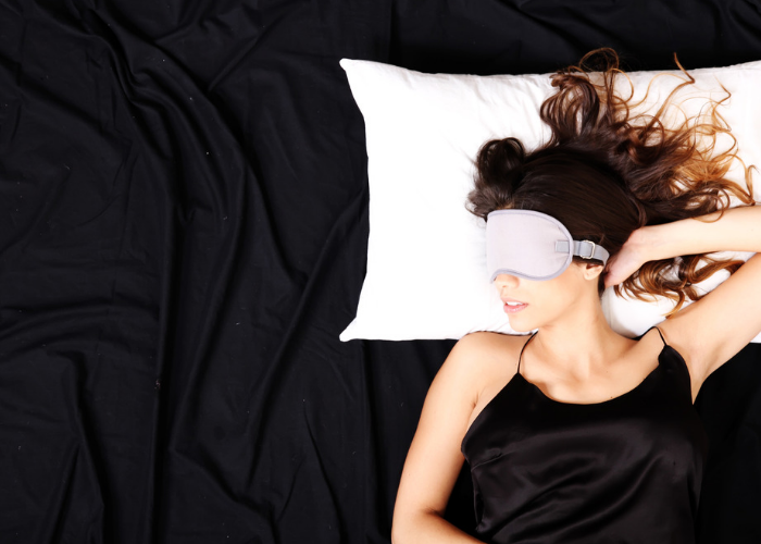 Woman with black bedsheets sleeping on a white pillow with white eyeshades