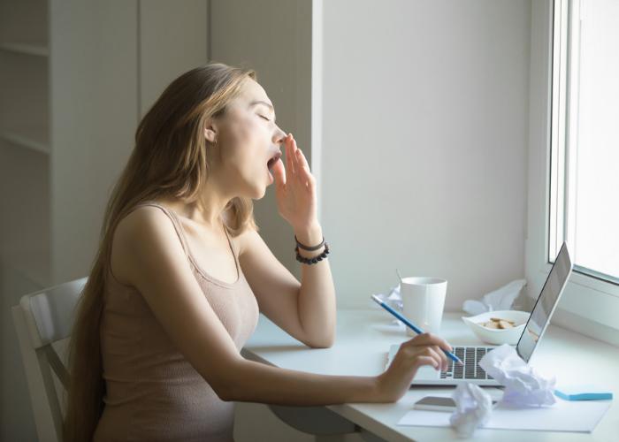 Woman trying to do work in the middle of yawning due to sleep deprivation