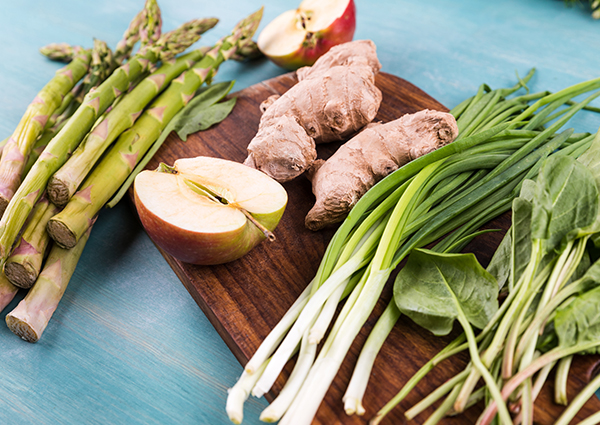 A spread of fresh produce including asparagus, halved apples, spinach, scallions, and fresh ginger on a cutting board