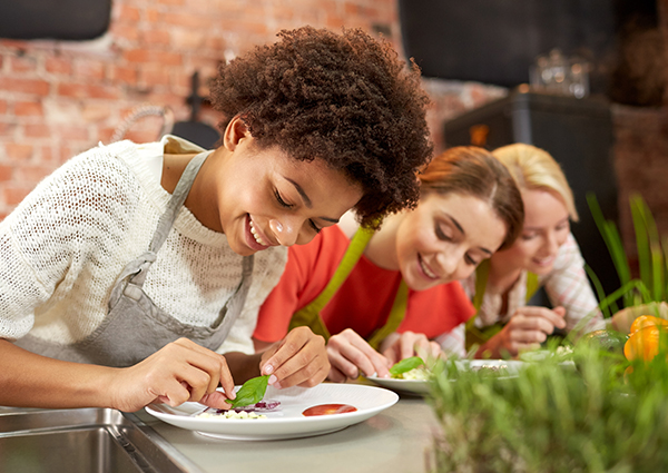 Three women in a vegan cooking class putting together a healthy vegan salad