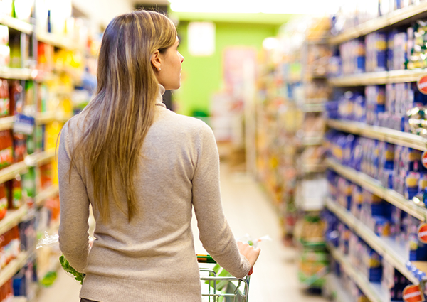 Woman with a shopping trolley in the grocery store looking at pasta