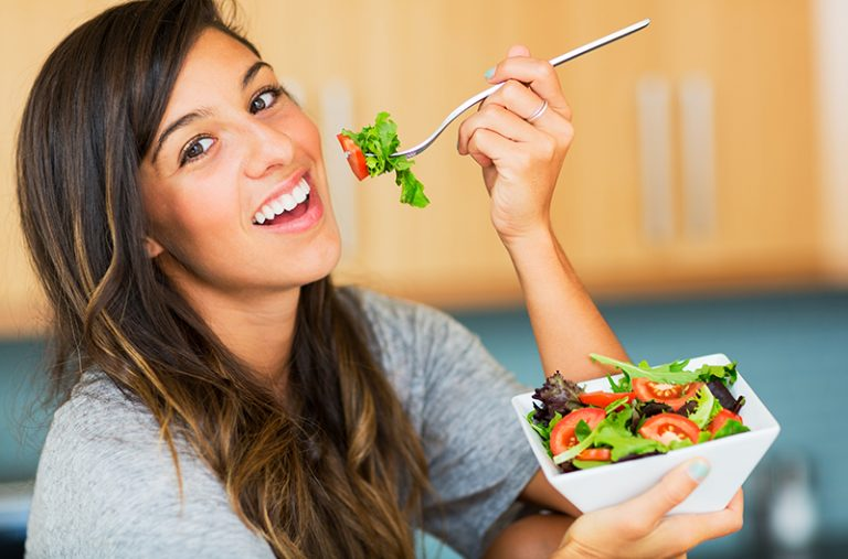 Woman smiling while eating a vegan salad