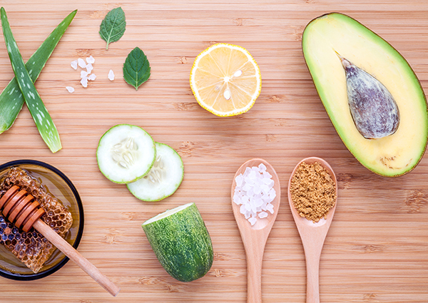 A flat lay of ingredients to make your own DIY face masks at home including half an avocado, aloe vera, fresh honey and honeycomb, cucumber slices, half a lemon, and salt.