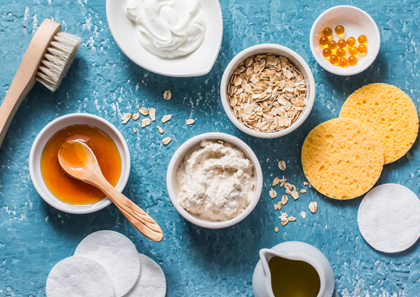 The ingredients for making a homemade oatmeal face make spread out on a blue table including oats, yogurt, and makeup pads