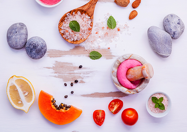 A colorful spread of ingredients to make DIY face masks including fresh lemon and papaya, along with a pestle and mortar, and salt