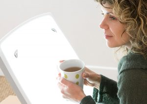Woman in a sweater holding a cup of hot coffee