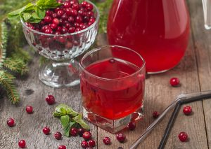 Glass of fresh cranberry juice in front of a bowl of whole cranberries and a jug of cranberry juice
